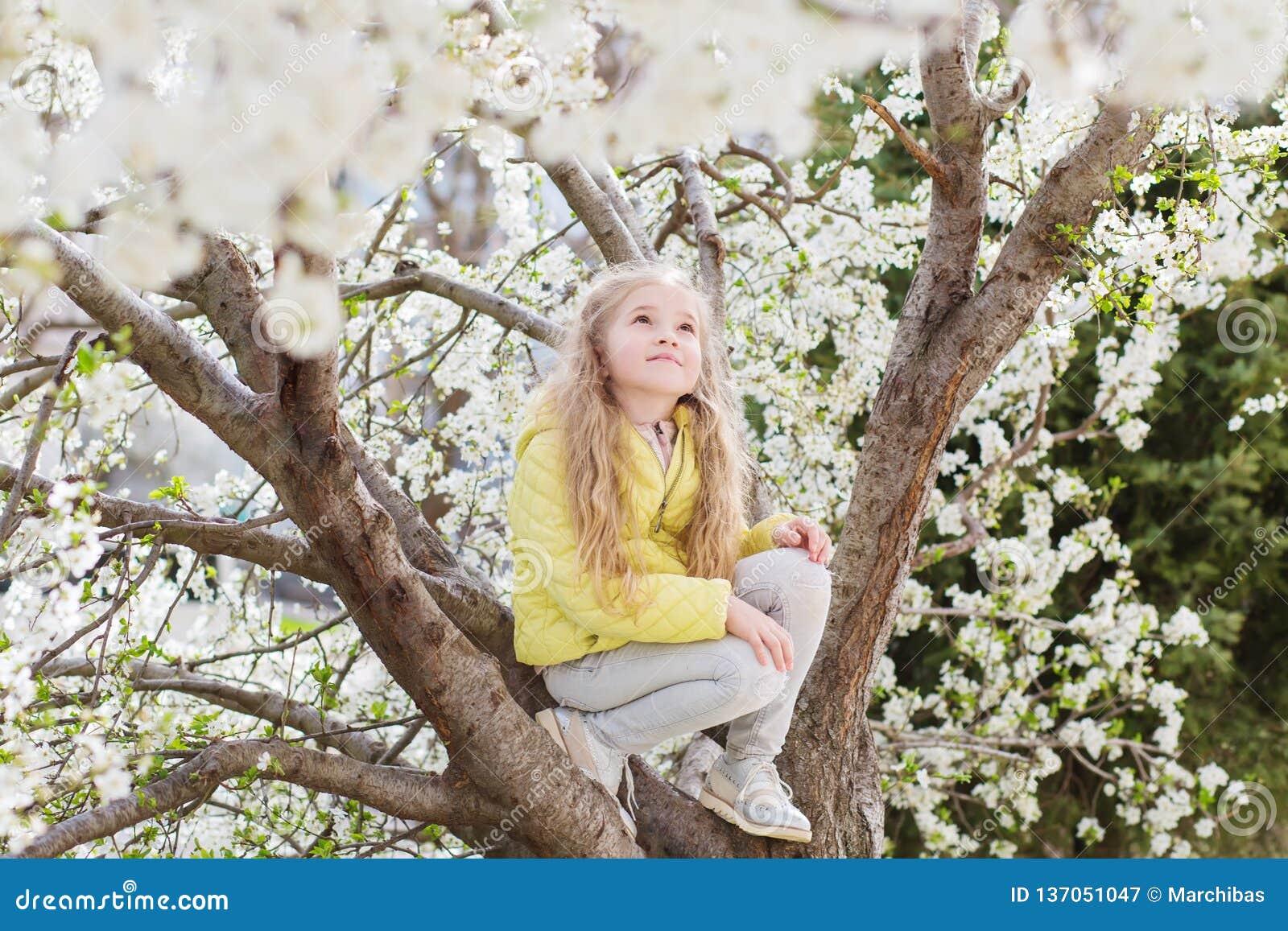 Menina adorável no jardim de florescência da árvore de cereja no dia de mola bonito