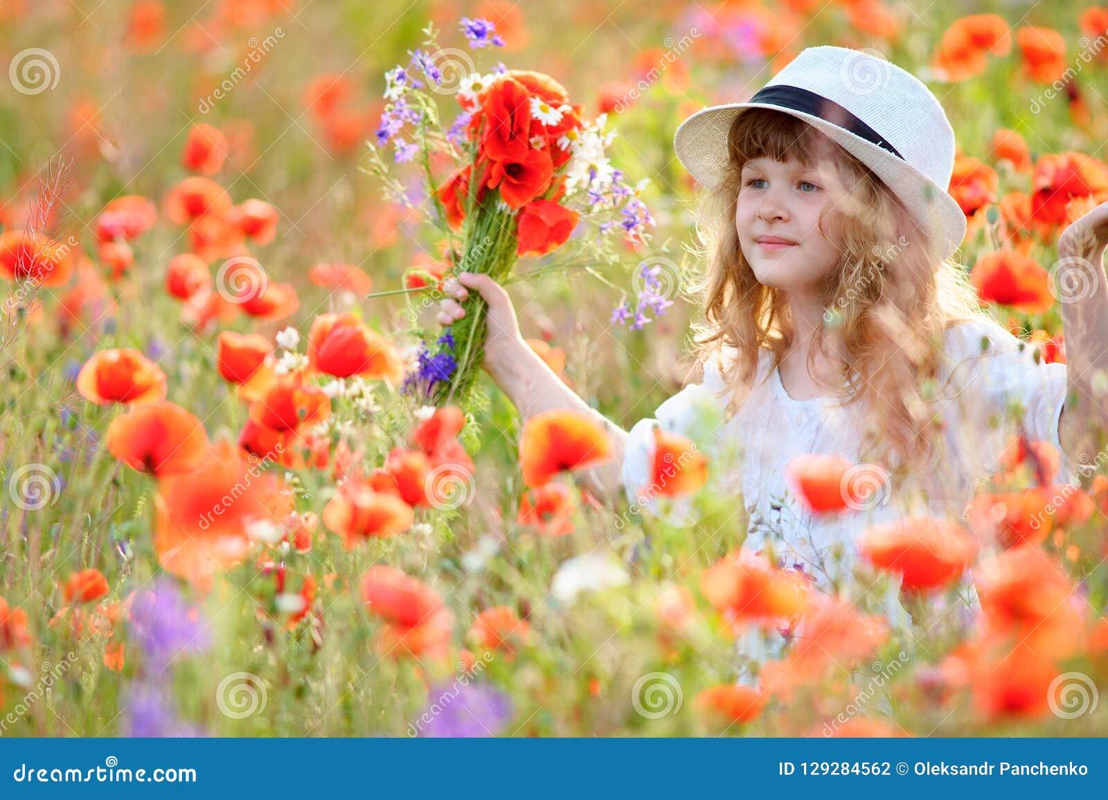 Menina adorável no vestido branco que joga no campo de flor da papoila
