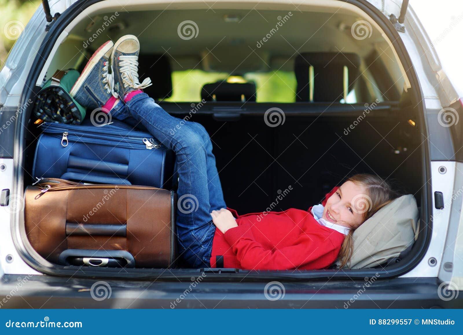 Menina adorável pronta para ir em férias com seus pais Caçoe o relaxamento em um carro antes de uma viagem por estrada