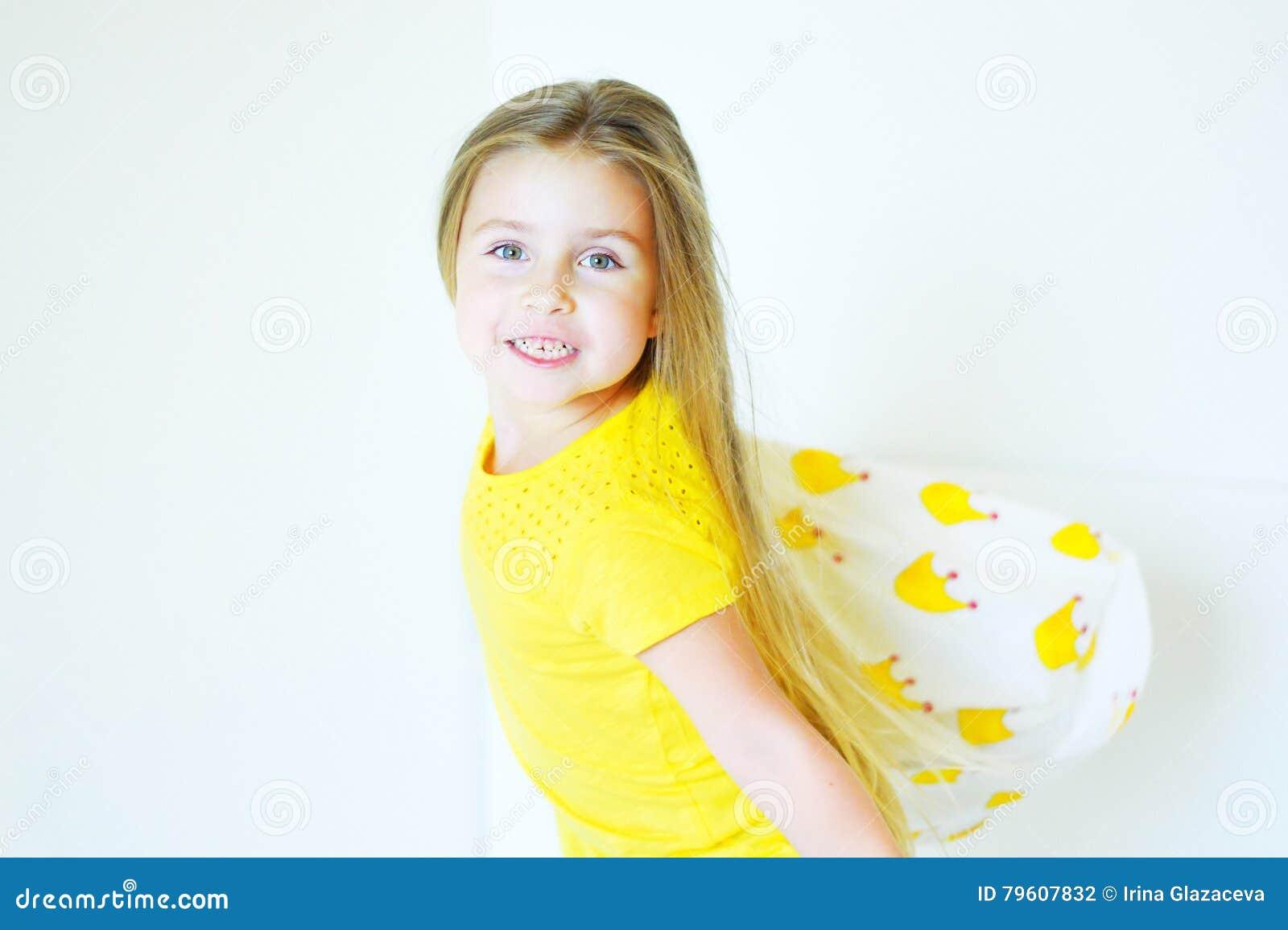 Menina adorável que joga com o descanso na cama em seu quarto