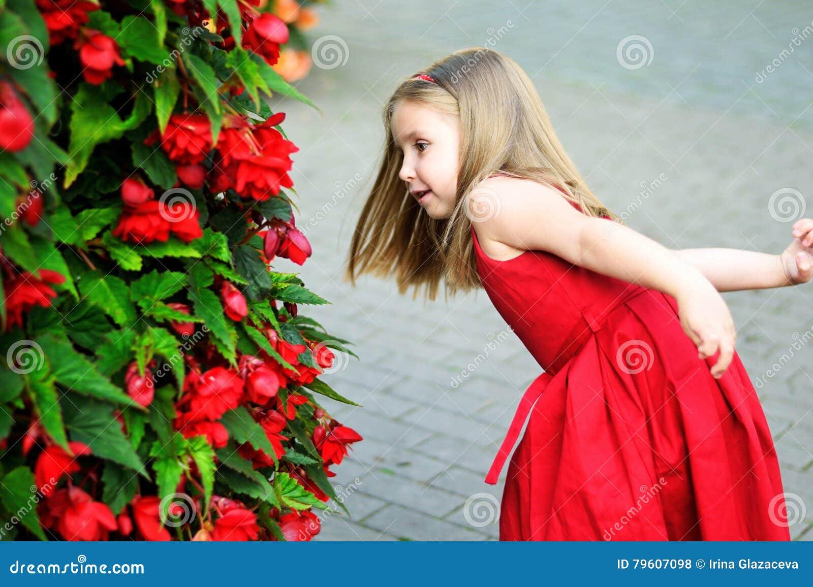 Menina adorável que joga perto do arbusto vermelho em um parque da cidade