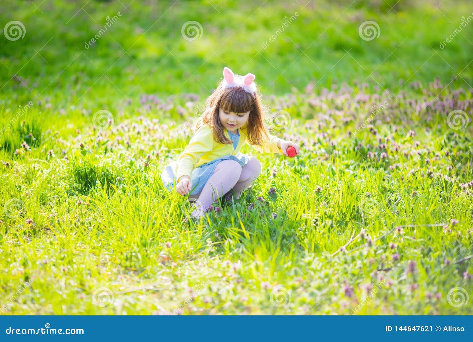 Menina adorável que senta-se na grama verde que joga no jardim na caça do ovo da páscoa