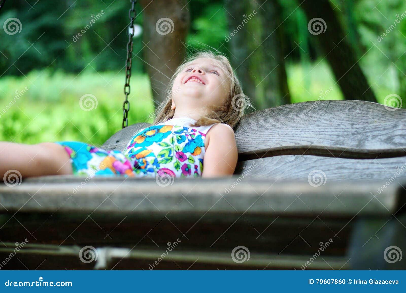 Menina adorável que tem o divertimento em um balanço de madeira no dia de verão