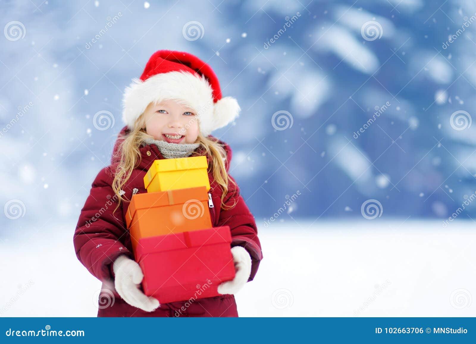 Menina adorável que veste o chapéu de Santa que guarda uma pilha de presentes do Natal no dia de inverno bonito