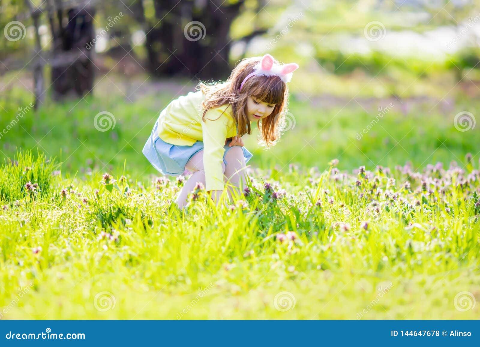 Menina ador?vel que senta-se na grama verde que joga no jardim na ca?a do ovo da p?scoa
