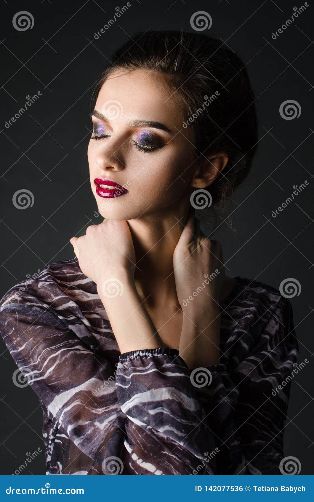 Menina adulta nova com composição de nivelamento bonita em um fundo preto