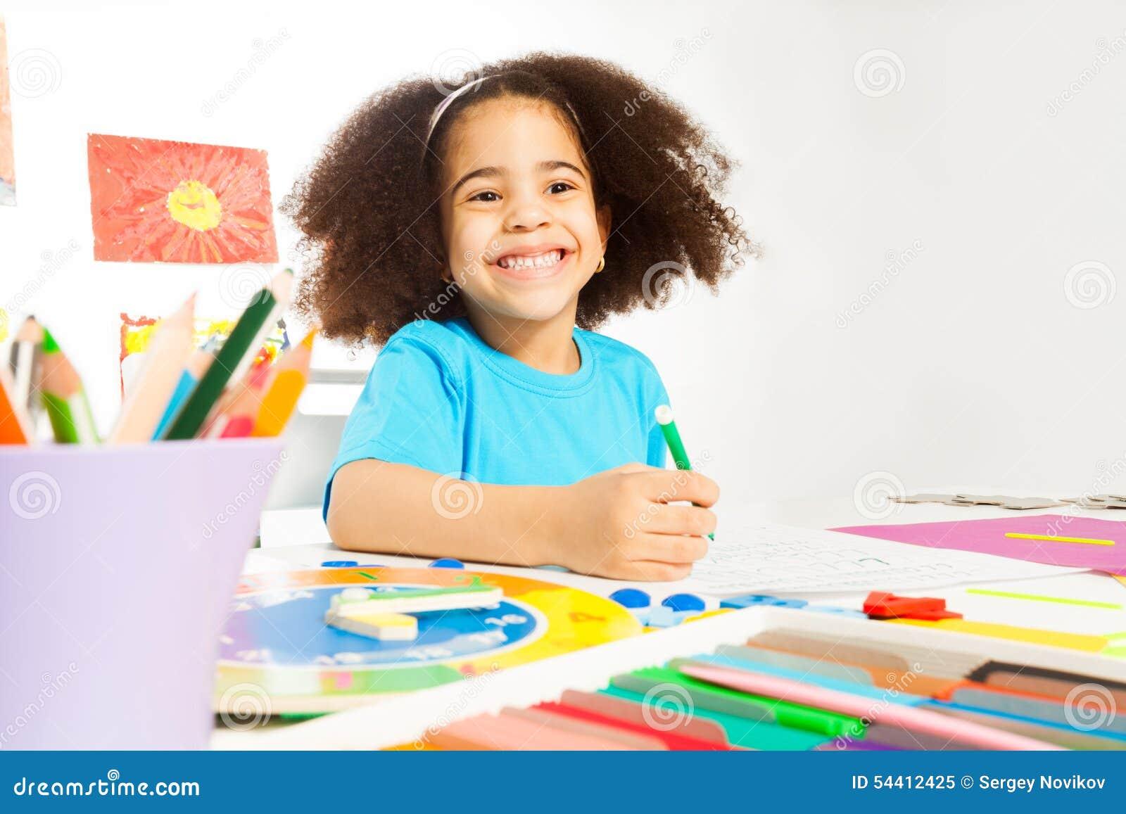 A menina africana feliz guarda letras da escrita do lápis