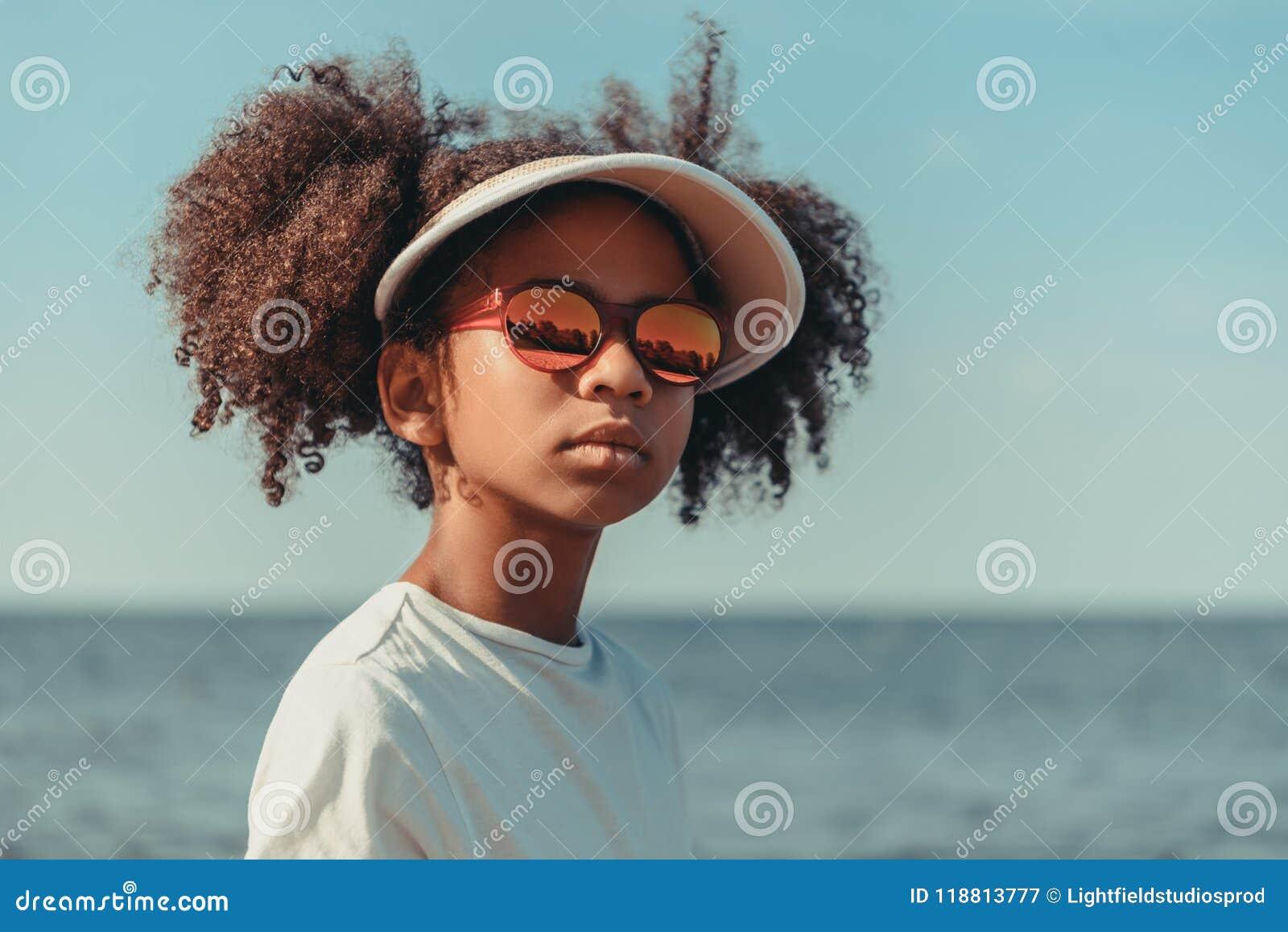Menina afro-americano bonita no tampão e nos óculos de sol que olham ausentes ao estar