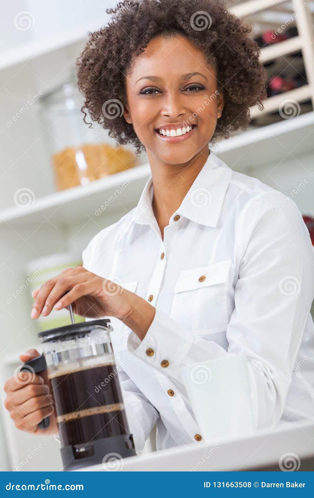 Menina afro-americano ou jovem mulher da raça misturada com os dentes perfeitos em sua cozinha que faz o café
