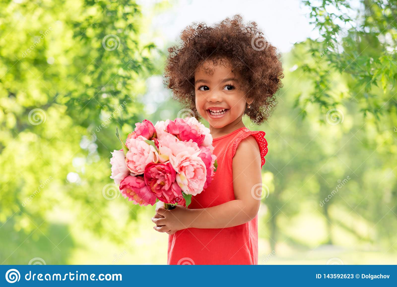 Menina afro-americano pequena feliz com flores
