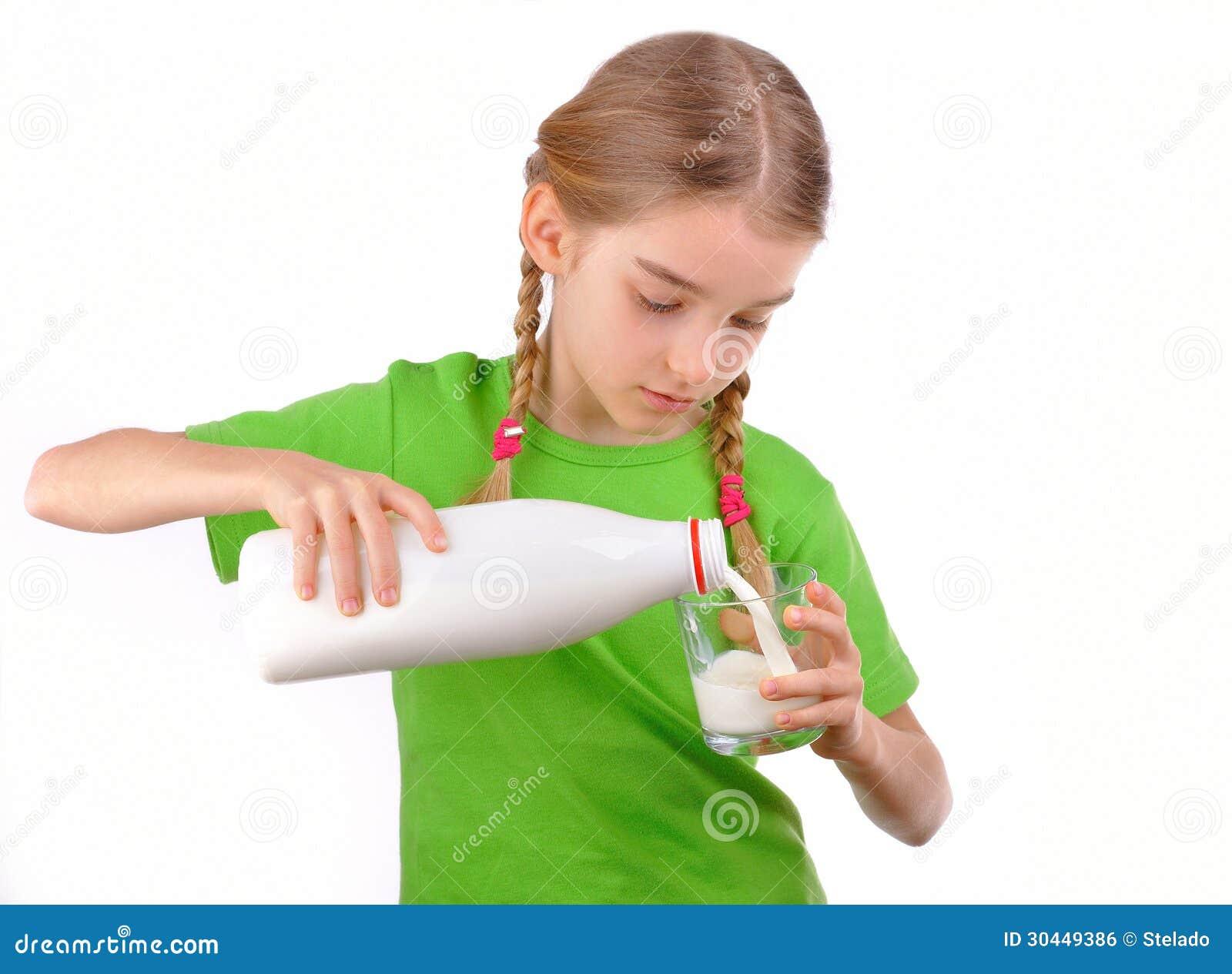 A menina agradável derrama o leite de uma garrafa no vidro