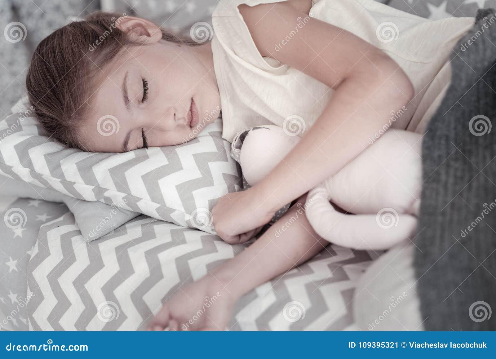 Menina agradável que dorme com seu brinquedo