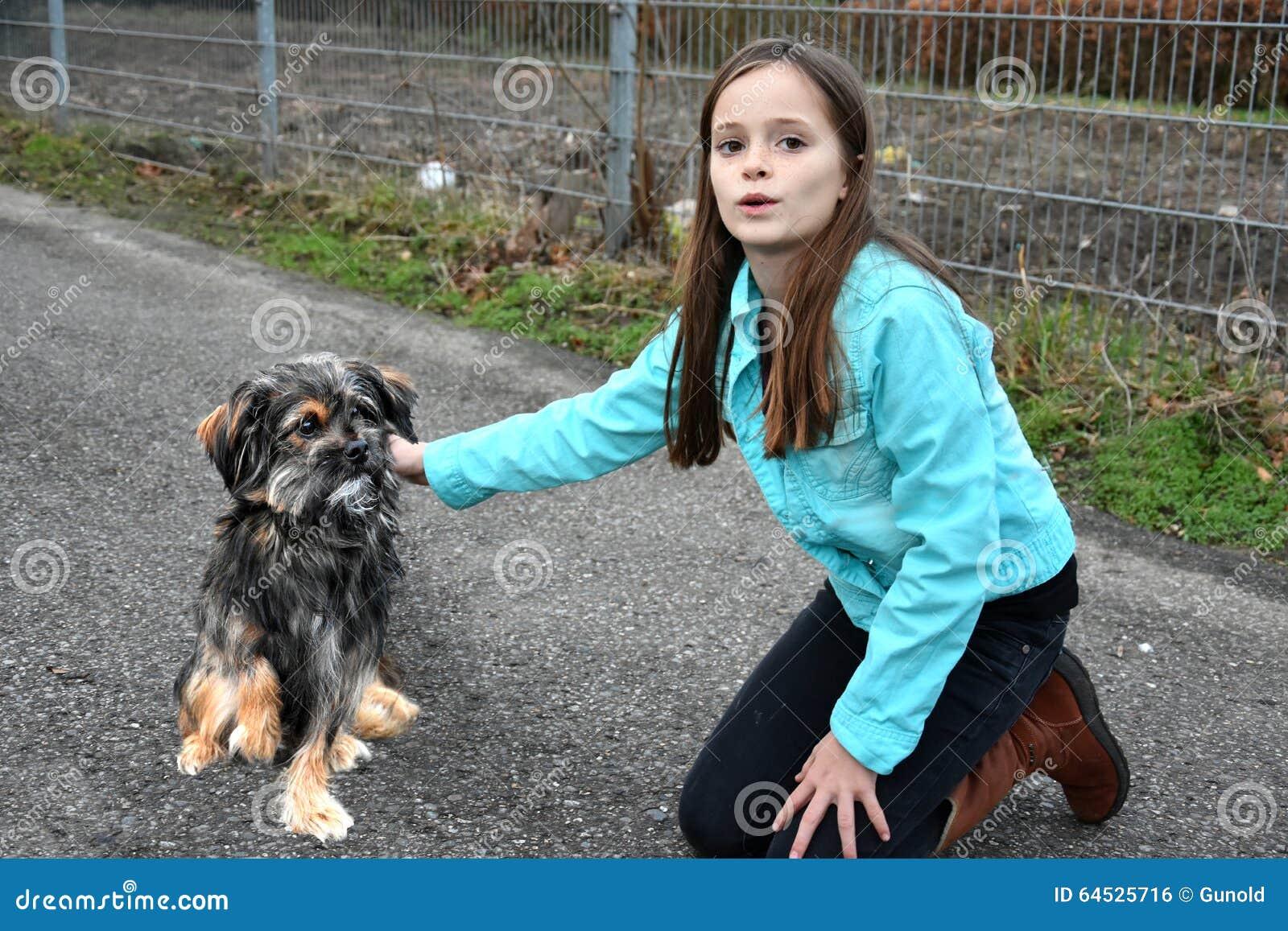 A menina ajuda o cão pequeno