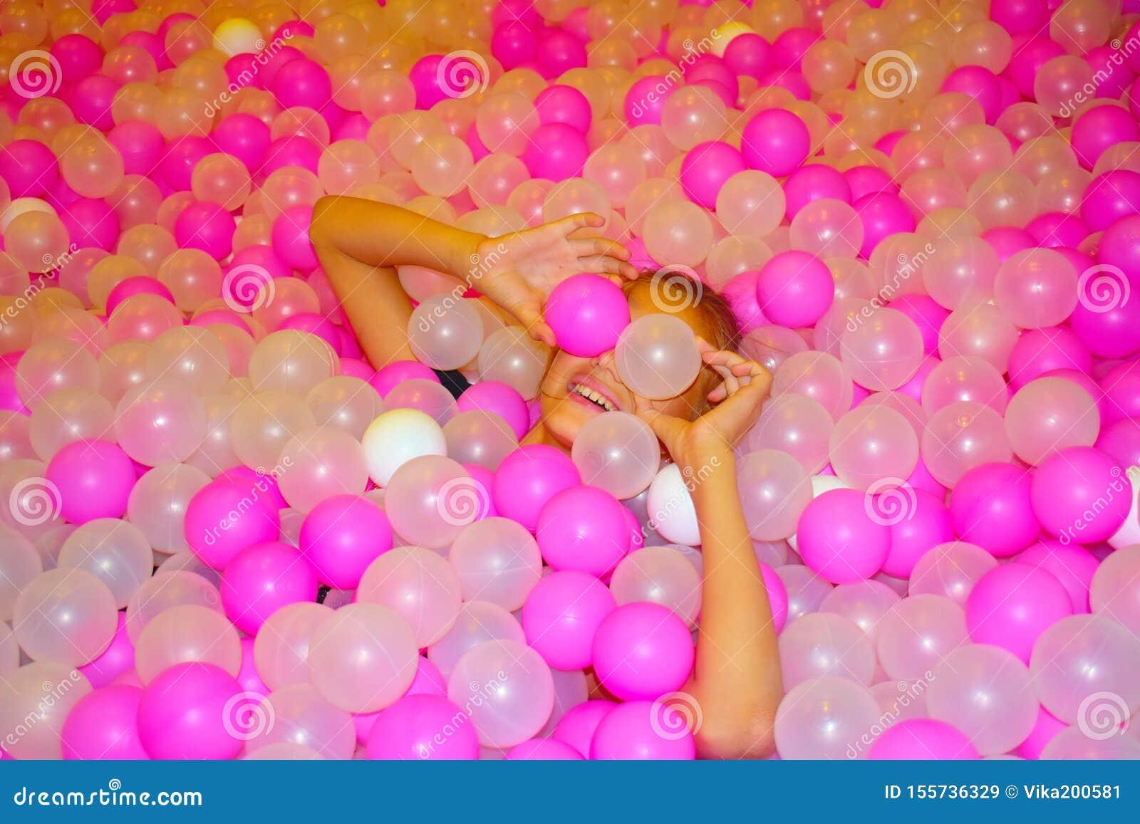 Menina alegre bonita com as bolas plásticas brilhantes do rosa Associação com bolas multi-coloridas