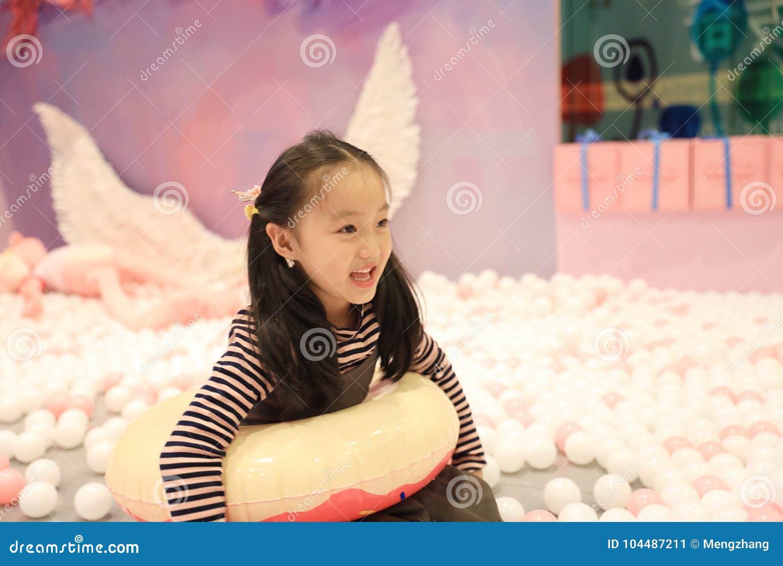 Menina alegre bonita que joga a terra de prazer no campo de jogos