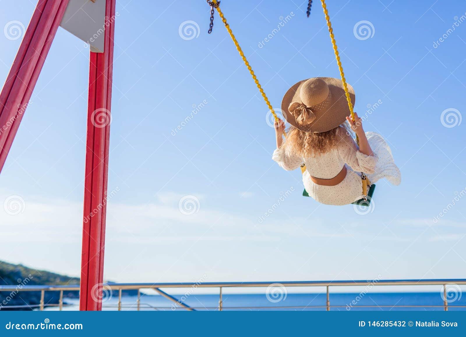 Menina alegre em uma equitação do chapéu e do vestido em um balanço que negligencia o mar