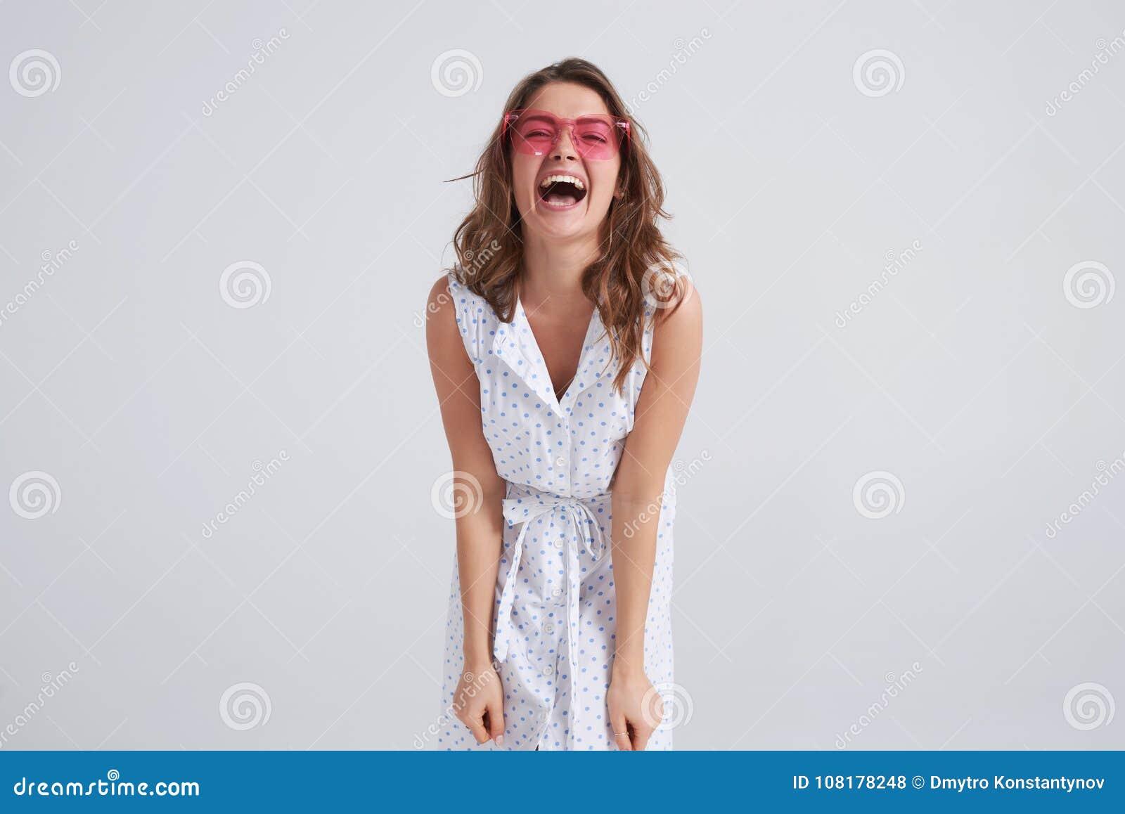 Menina alegre nos óculos de sol cor-de-rosa que vão loucos fazendo a cara engraçada