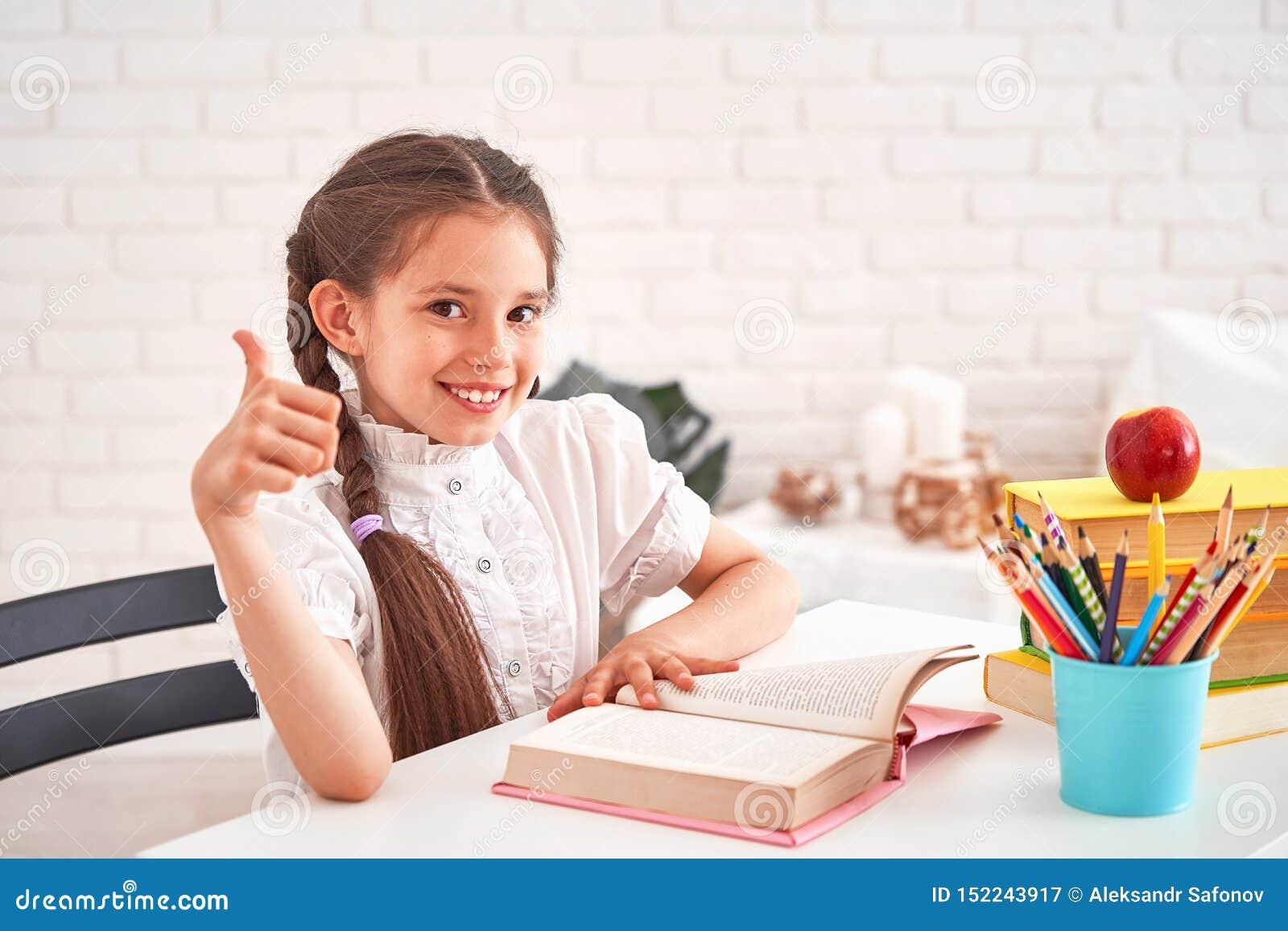 Menina alegre que senta-se na tabela com lápis e livros de texto Aluno feliz da criança que faz trabalhos de casa na tabela Bonit