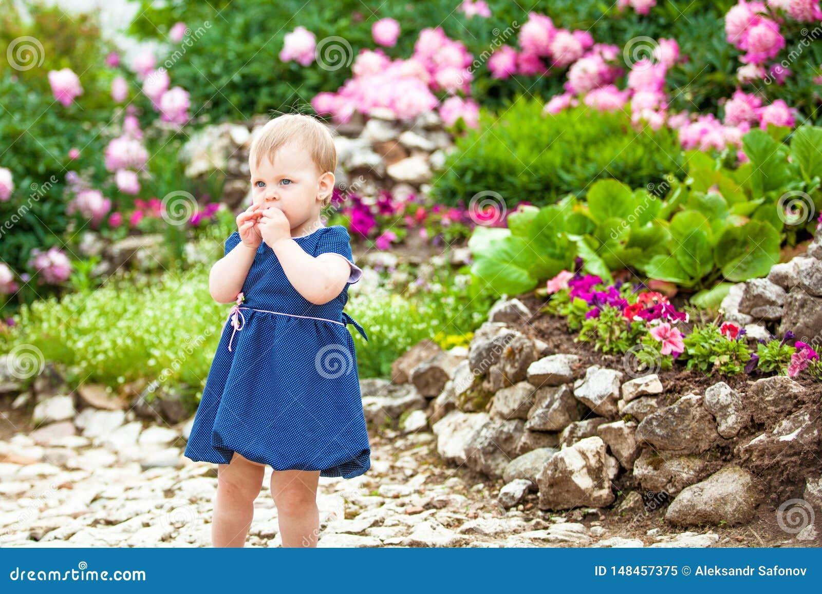 A menina anda no parque com camas de flor