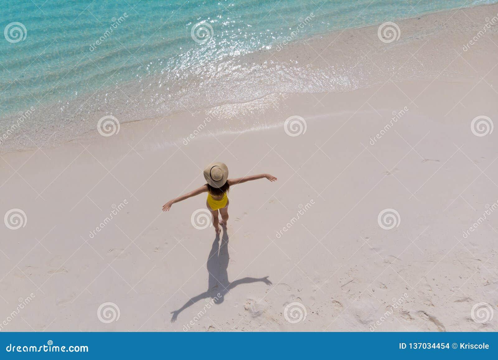 A menina apenas no litoral e aprecia o sol Jovem mulher em um chapéu de palha e suportes amarelos do roupa de banho com os braços