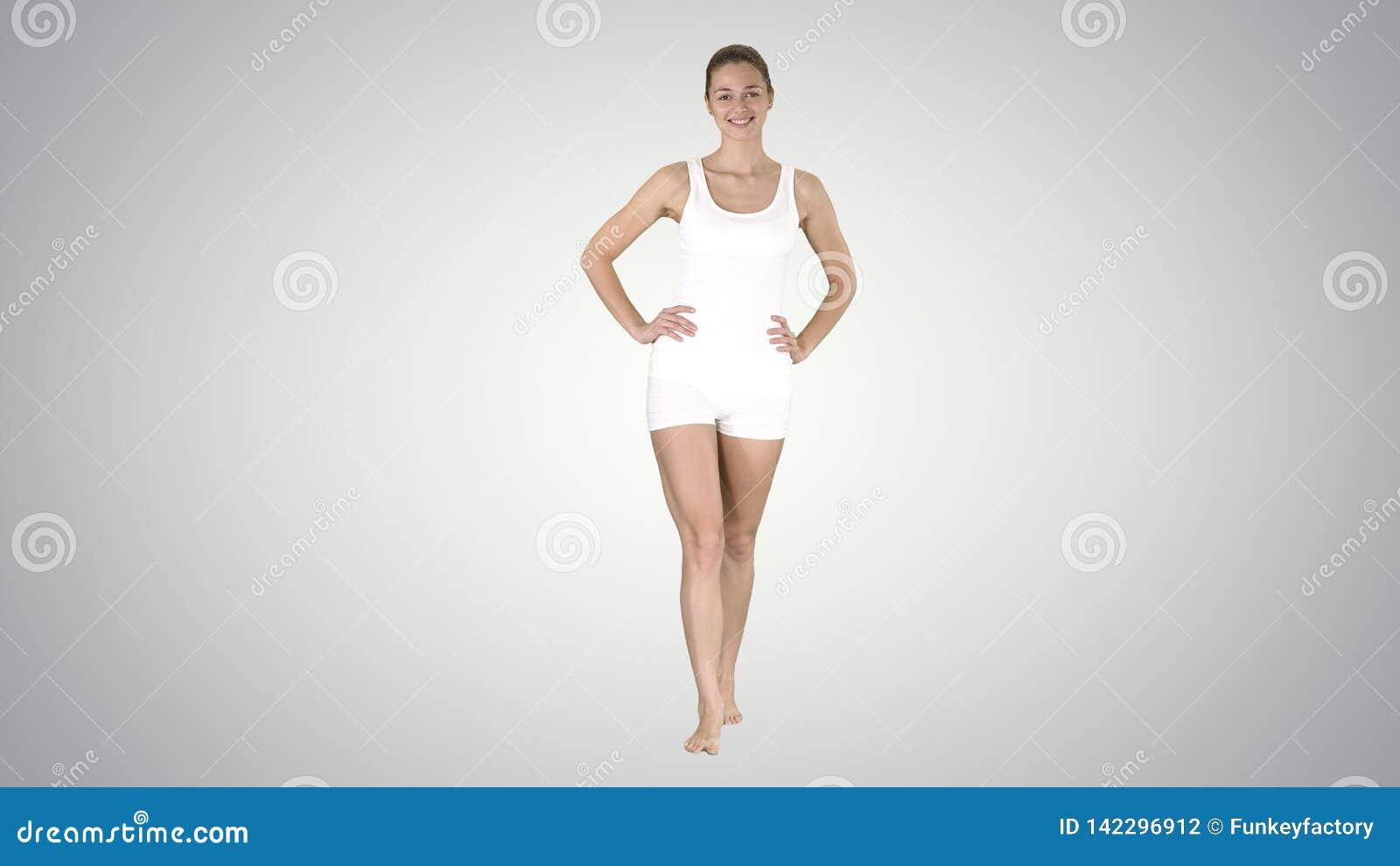 Menina apta e desportiva no roupa interior do inclinação que anda com os pés descalços com mãos em seus quadris no fundo do incli