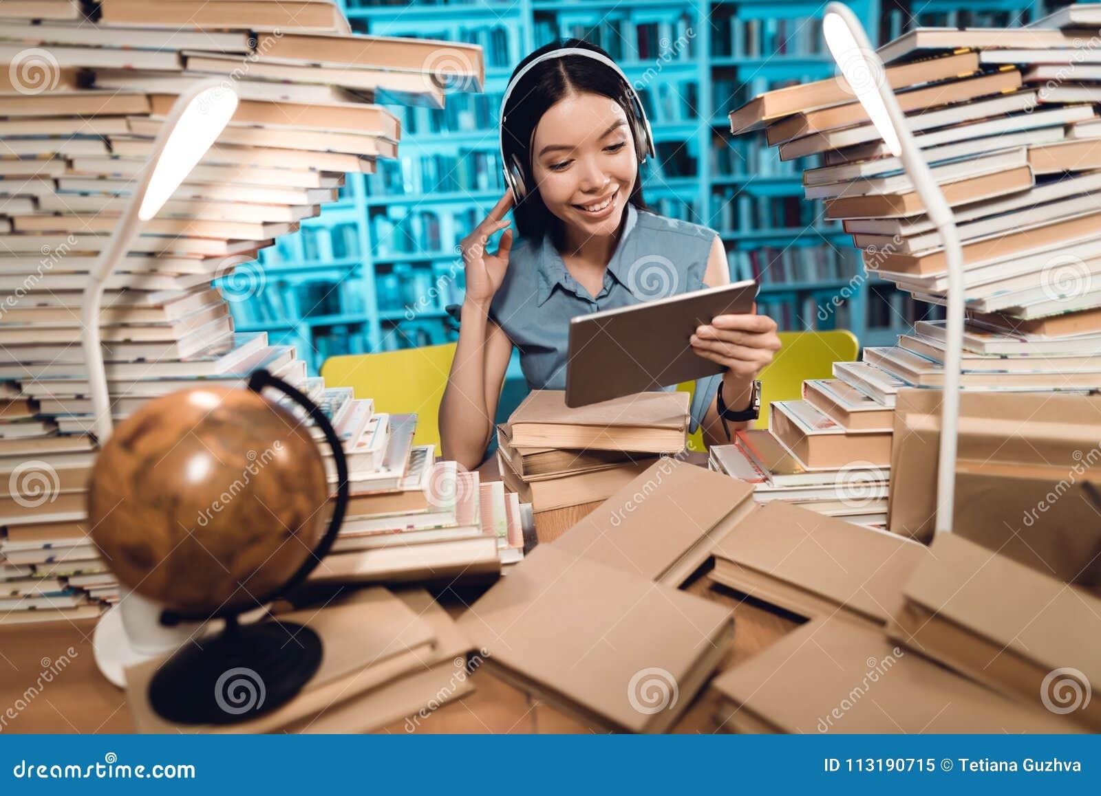 Menina asiática étnica cercada por livros na biblioteca na noite O estudante está escutando a música na tabuleta