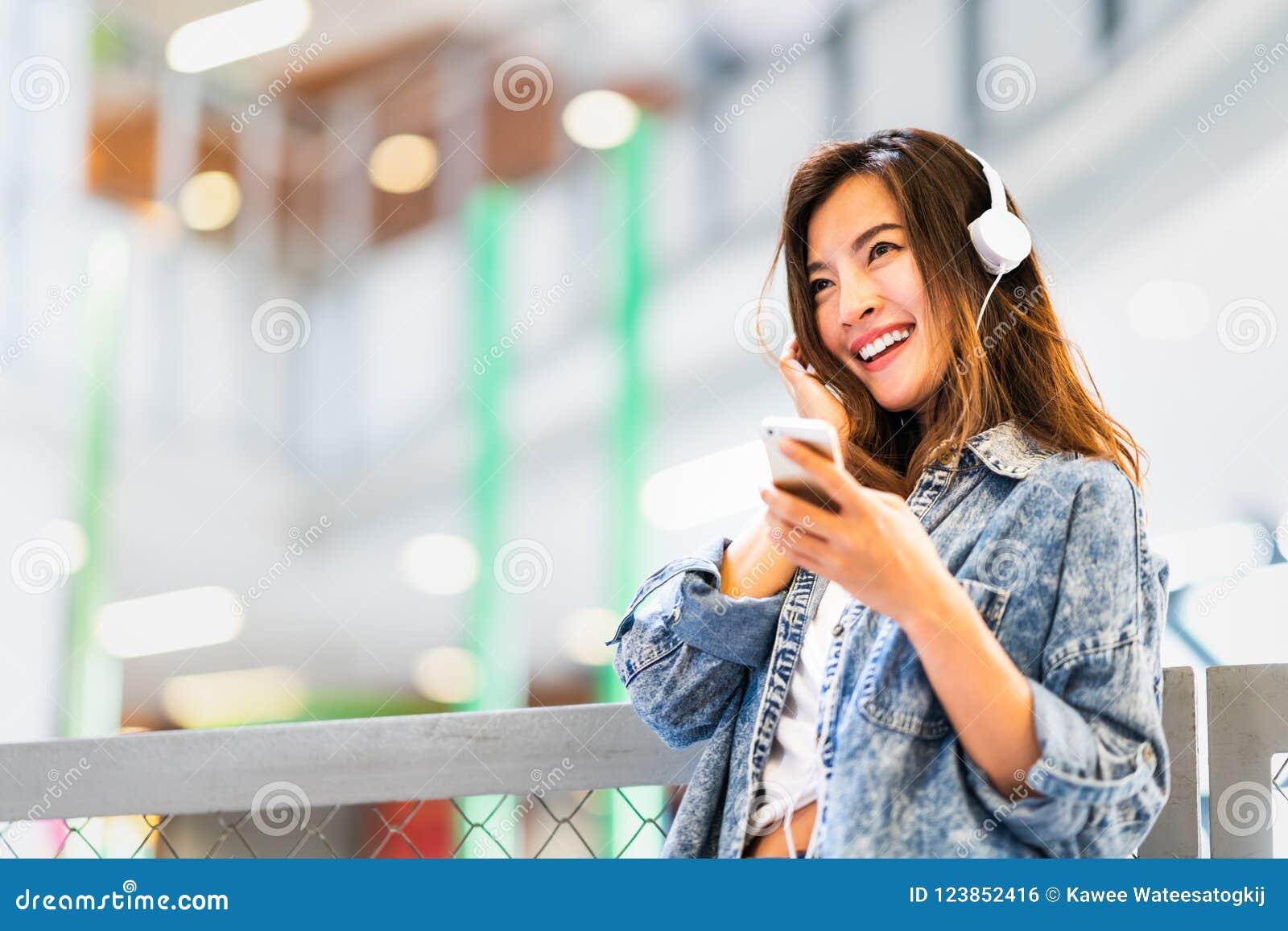 A menina asiática bonita escuta a música usando o sorriso do smartphone e do fones de ouvido no espaço da cópia, no passatempo ou
