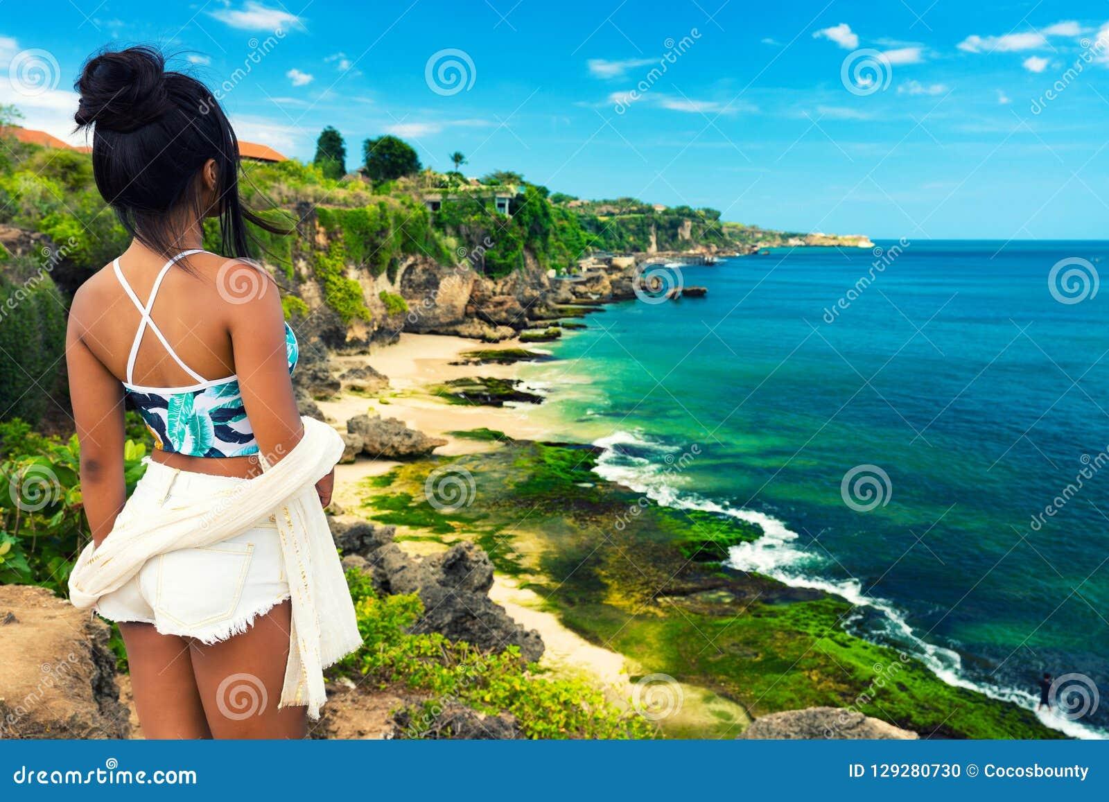 A menina asiática bonita nova no biquini aprecia férias de verão na praia tropical Férias de verão e conceito do estilo de vida