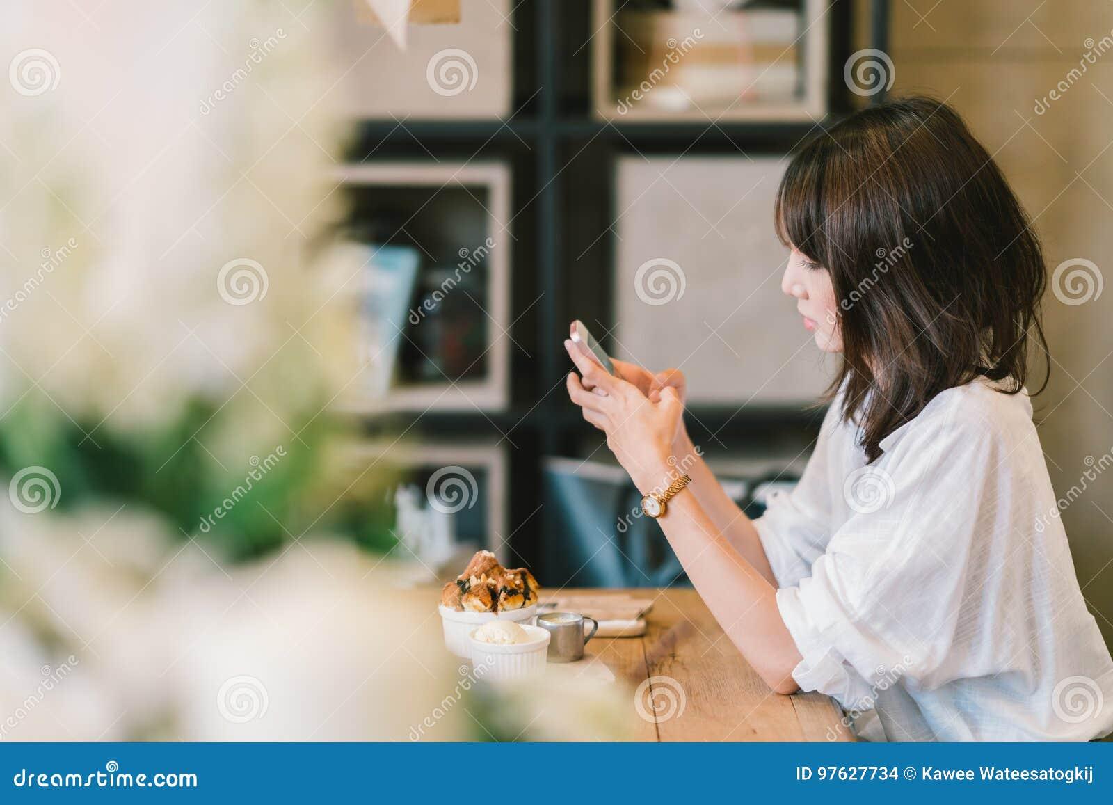 Menina asiática bonita que usa o smartphone no café com brinde do chocolate e gelado Sobremesa da cafetaria e estilo de vida ocas