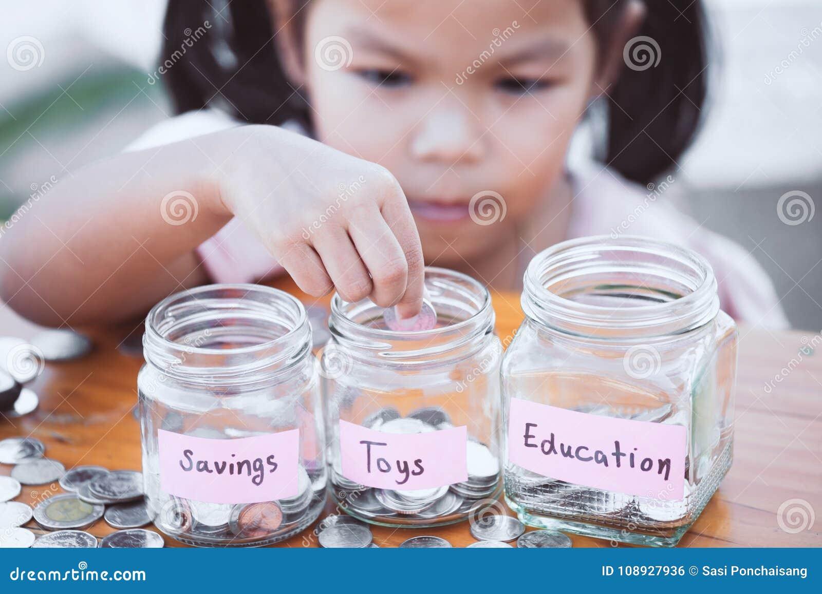Menina asiática bonito da criança pequena que põe a moeda na garrafa de vidro