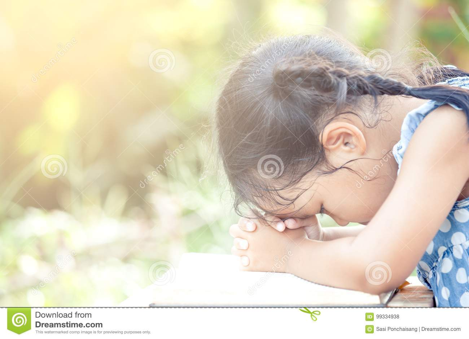 Menina asiática bonito da criança pequena que reza com dobrado sua mão
