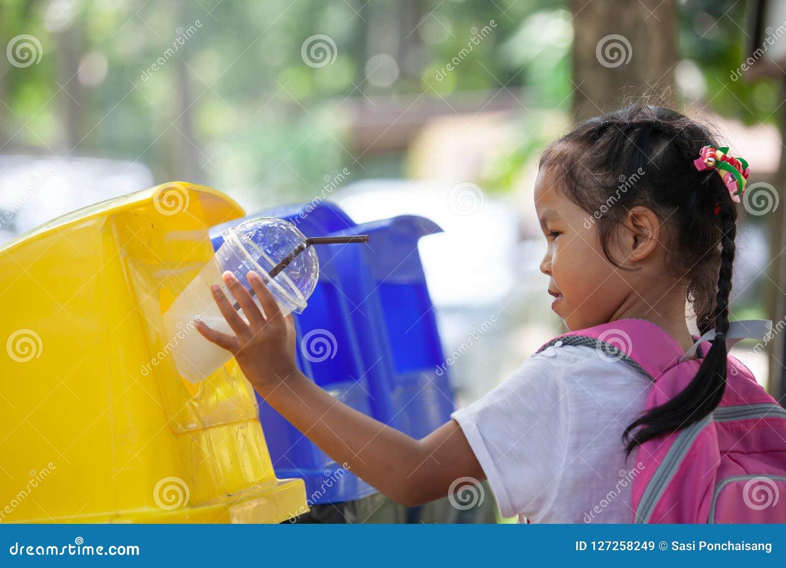 Menina asiática bonito da criança que joga o vidro plástico em reciclar o lixo