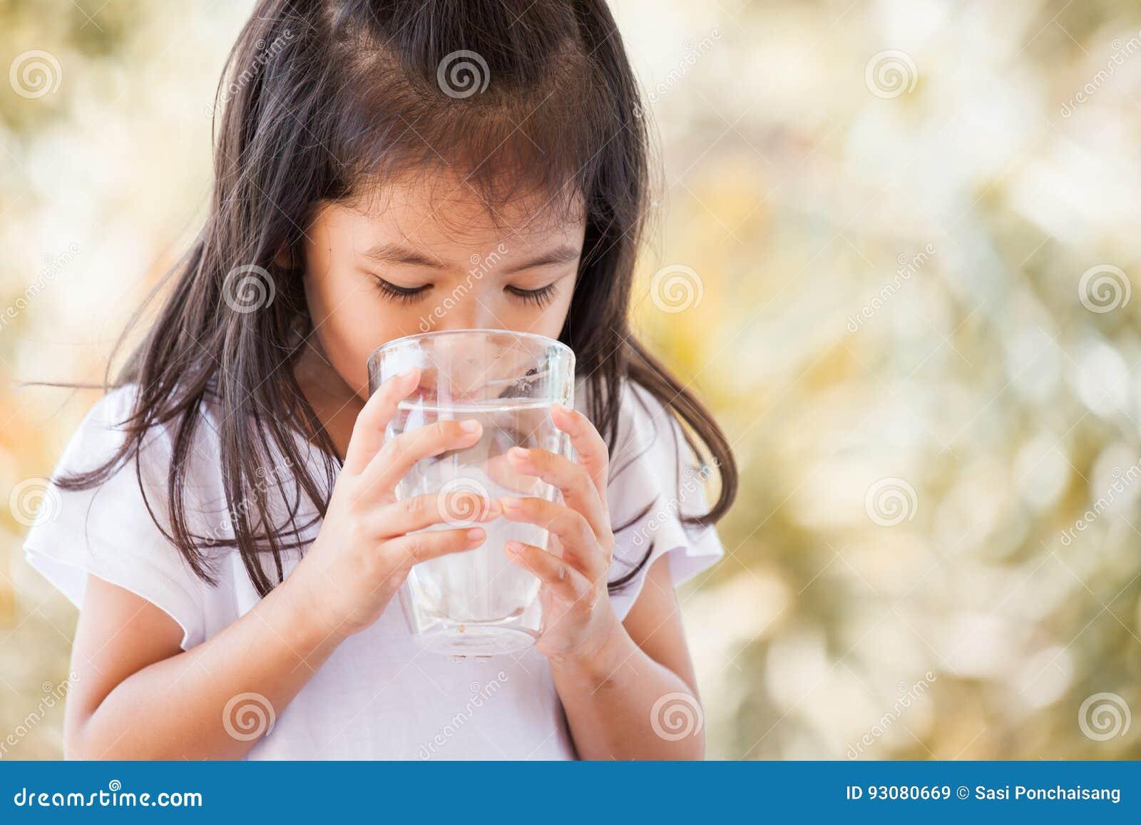 Menina asiática bonito que bebe a água fresca do vidro