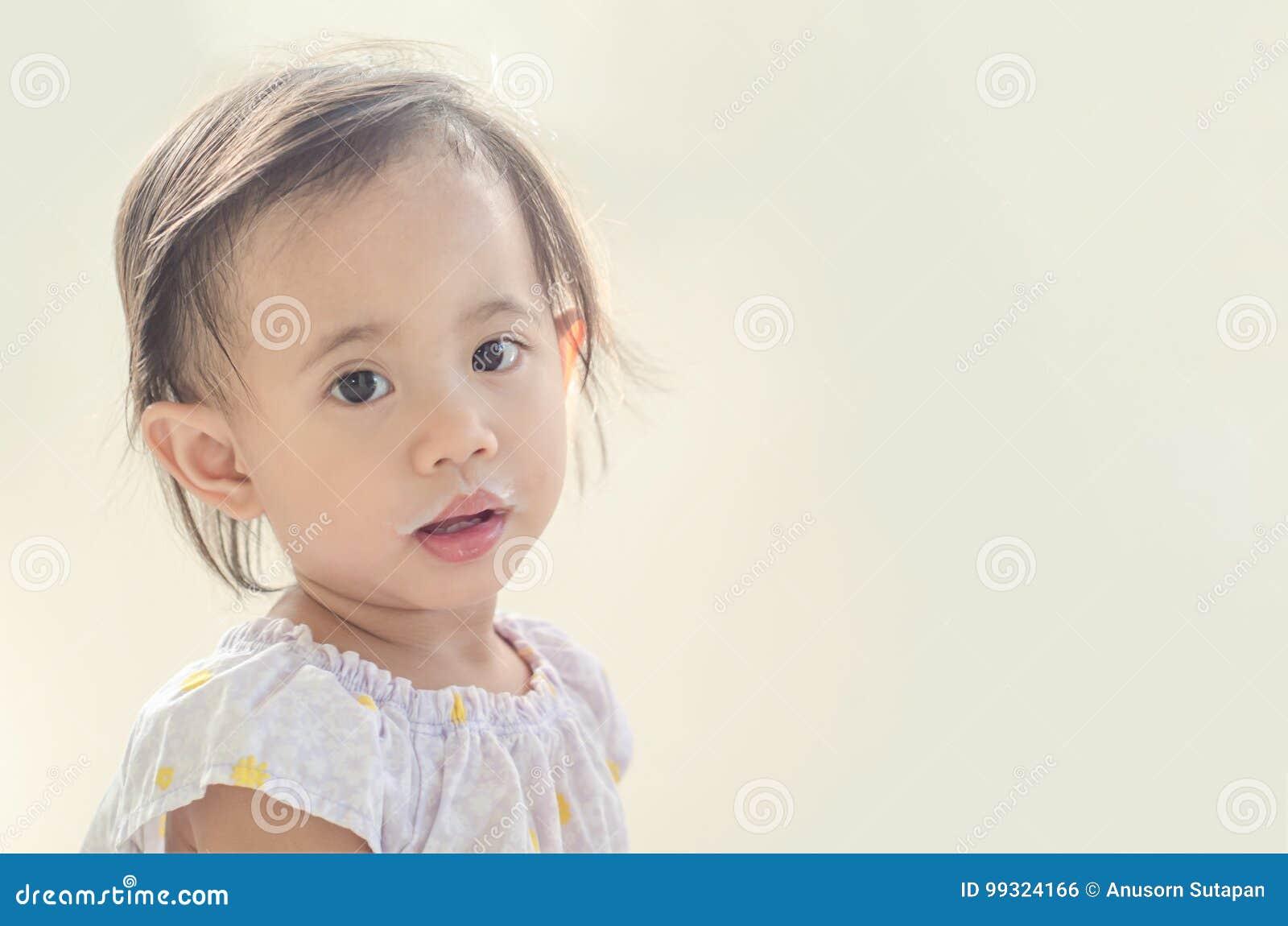 Menina asiática da criança com a boca suja do leite