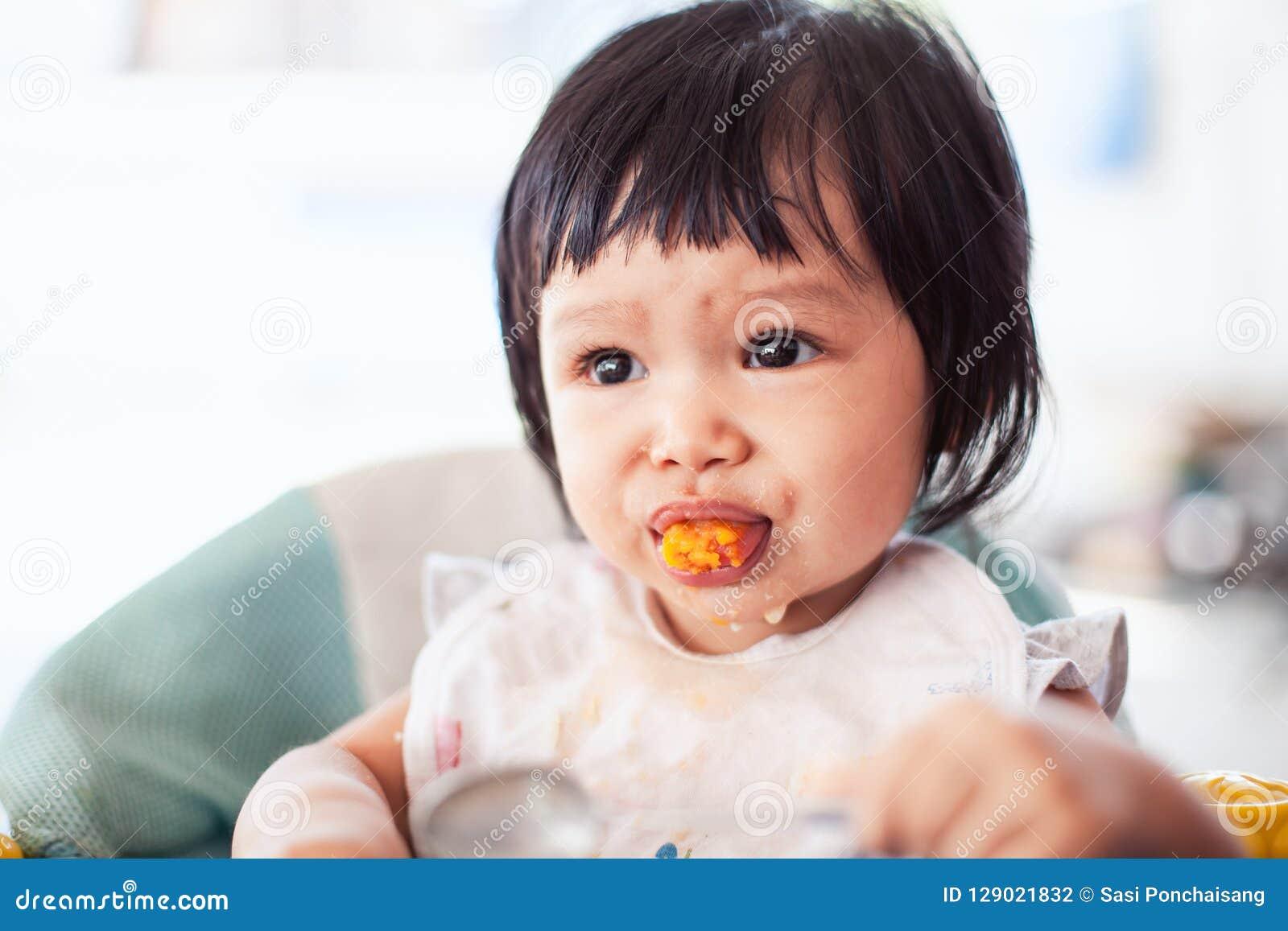 Menina asiática da criança do bebê bonito que come o alimento saudável só