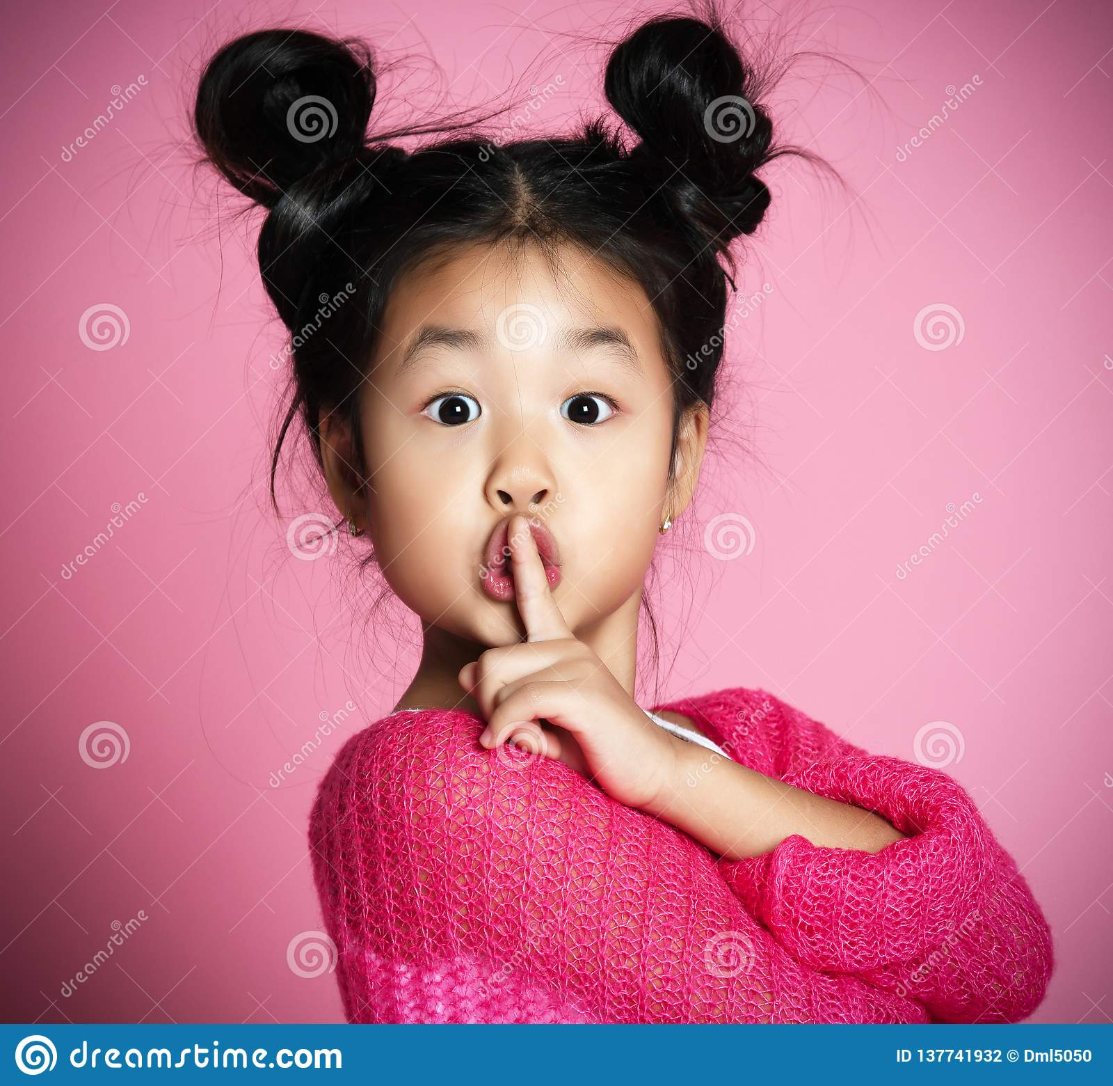 A menina asiática da criança na camiseta cor-de-rosa mostra shh o fim do sinal acima do retrato