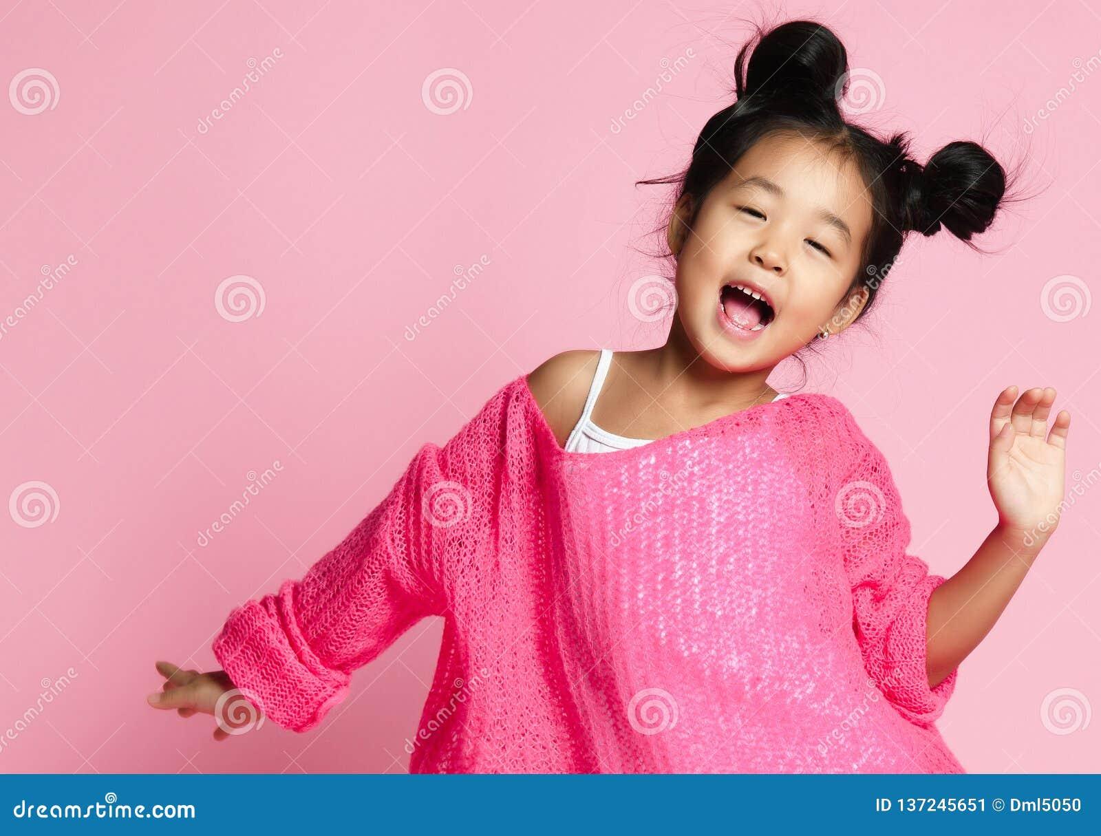A menina asiática da criança na camiseta cor-de-rosa, nas calças brancas e em bolos engraçados canta Fim acima