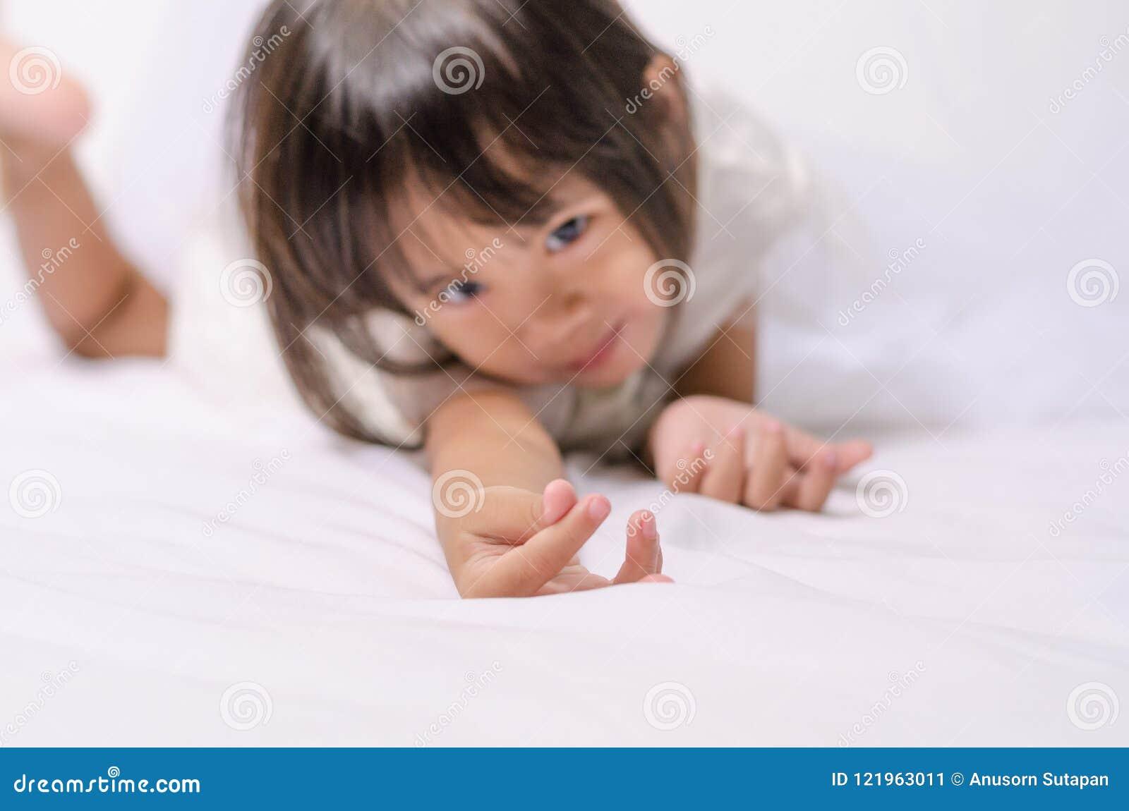 Menina asiática da criança da criança que faz o mini sinal do coração por sua mão