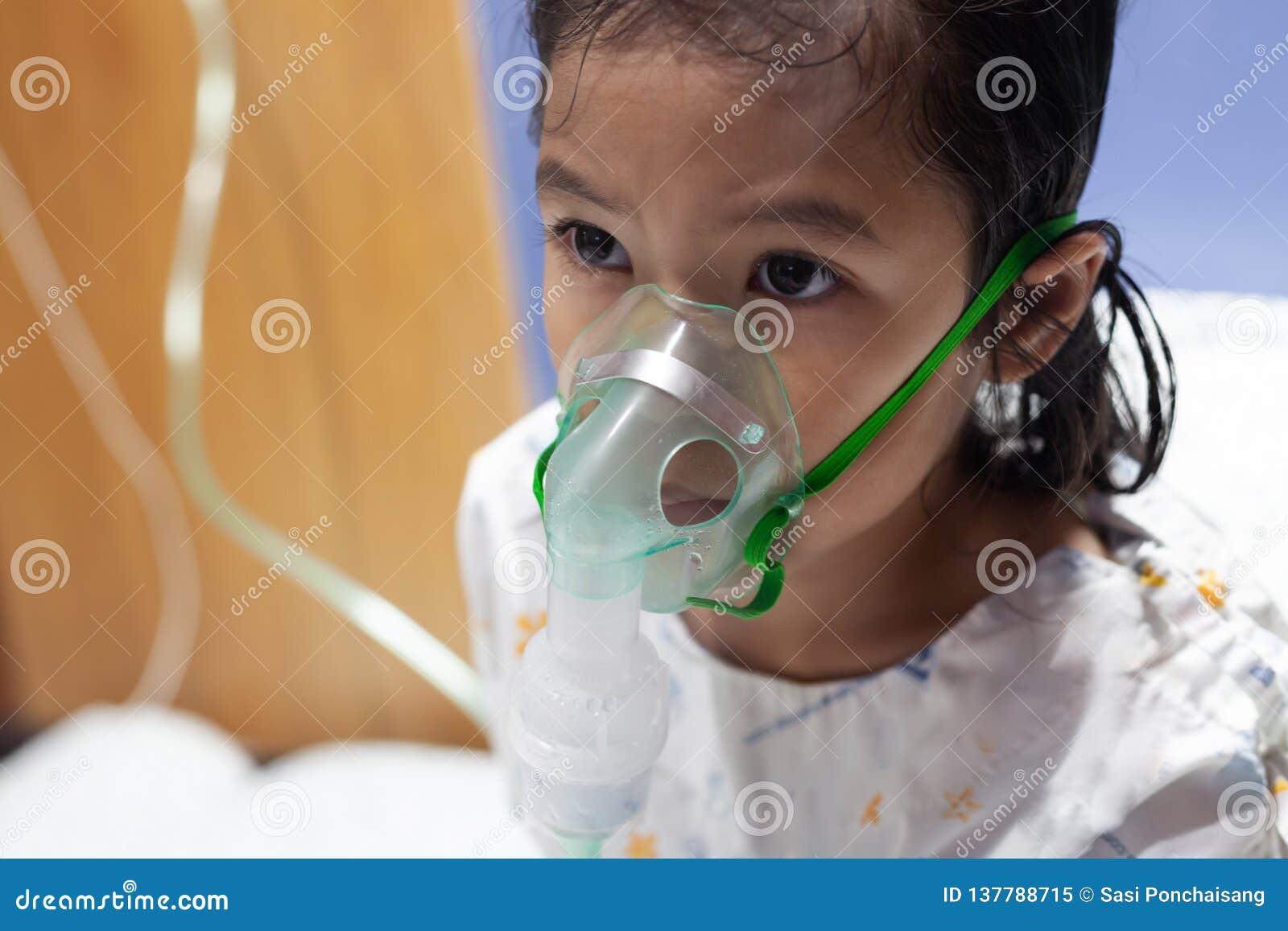 A menina asiática está com a asma ou o nebulization da doença e da necessidade da pneumonia obtém perto a máscara do inalador em