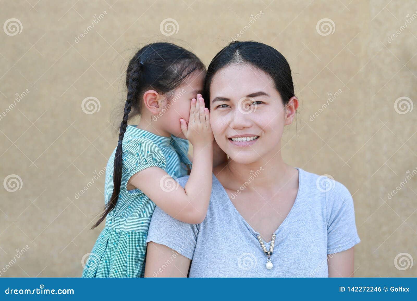 Menina asiática feliz da criança que compartilha de um segredo a sua mamã Bisbolhetice de sussurro da menina da criança um algo s