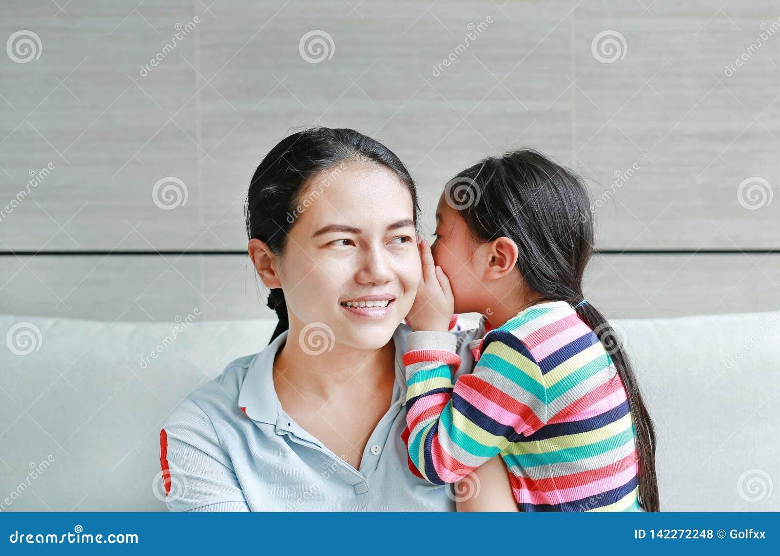 Menina asiática feliz da criança que compartilha de um segredo a sua mamã na sala de visitas em casa Bisbolhetice de sussurro da