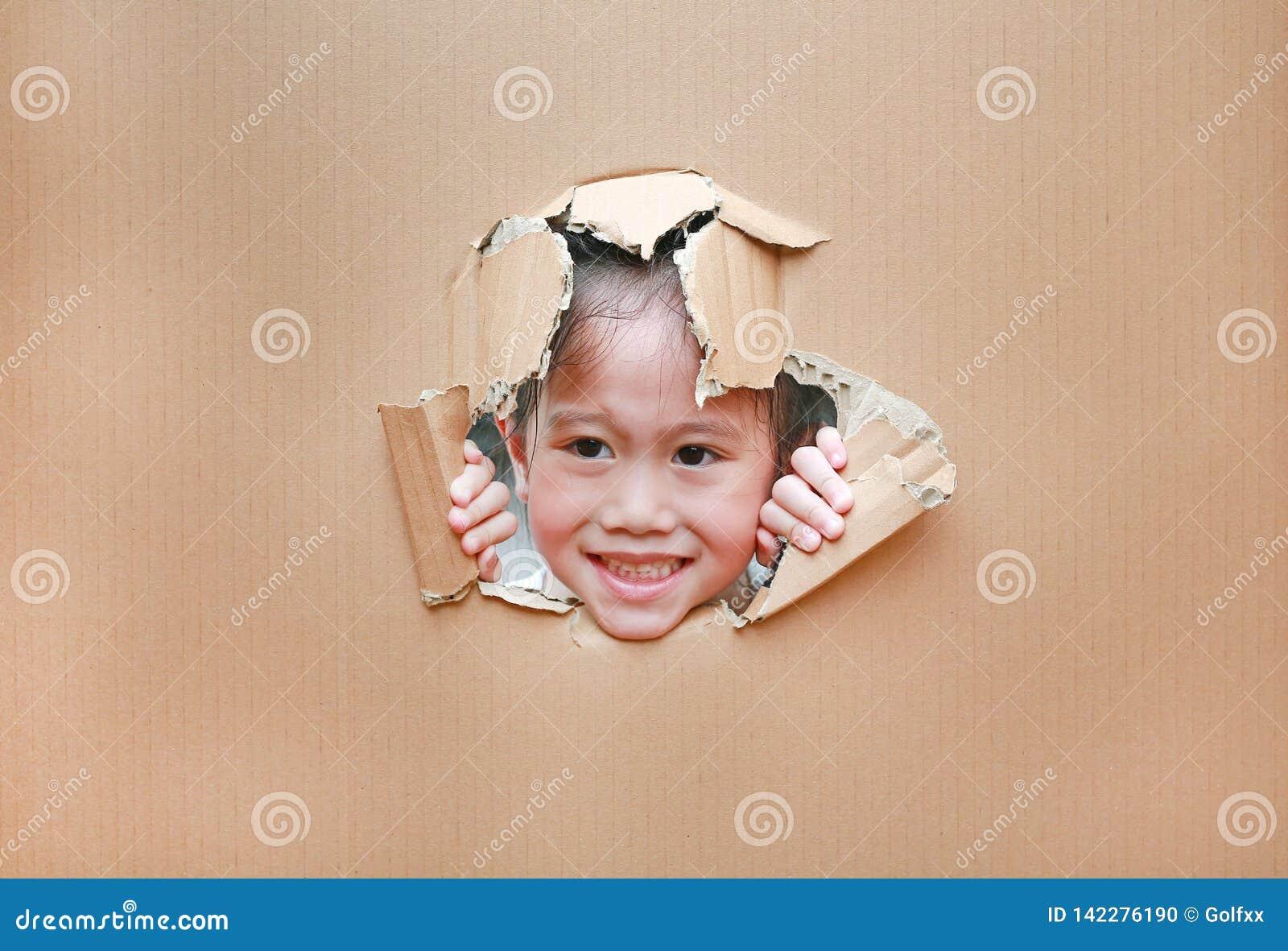 Menina asiática feliz da criança que olha através do furo no cartão com espaço da cópia