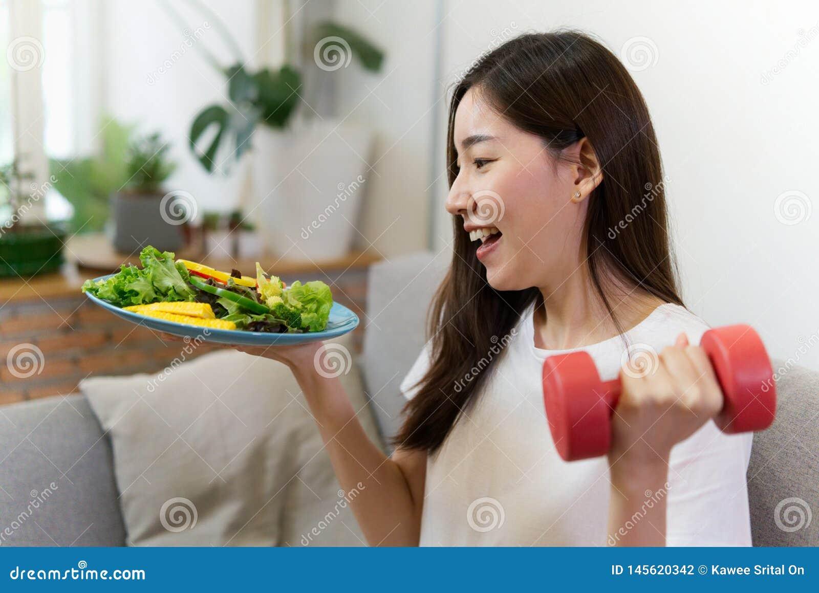 A menina asiática nova que guarda a salada e o peso vermelho está sentando-se no sofá com cara do sorriso