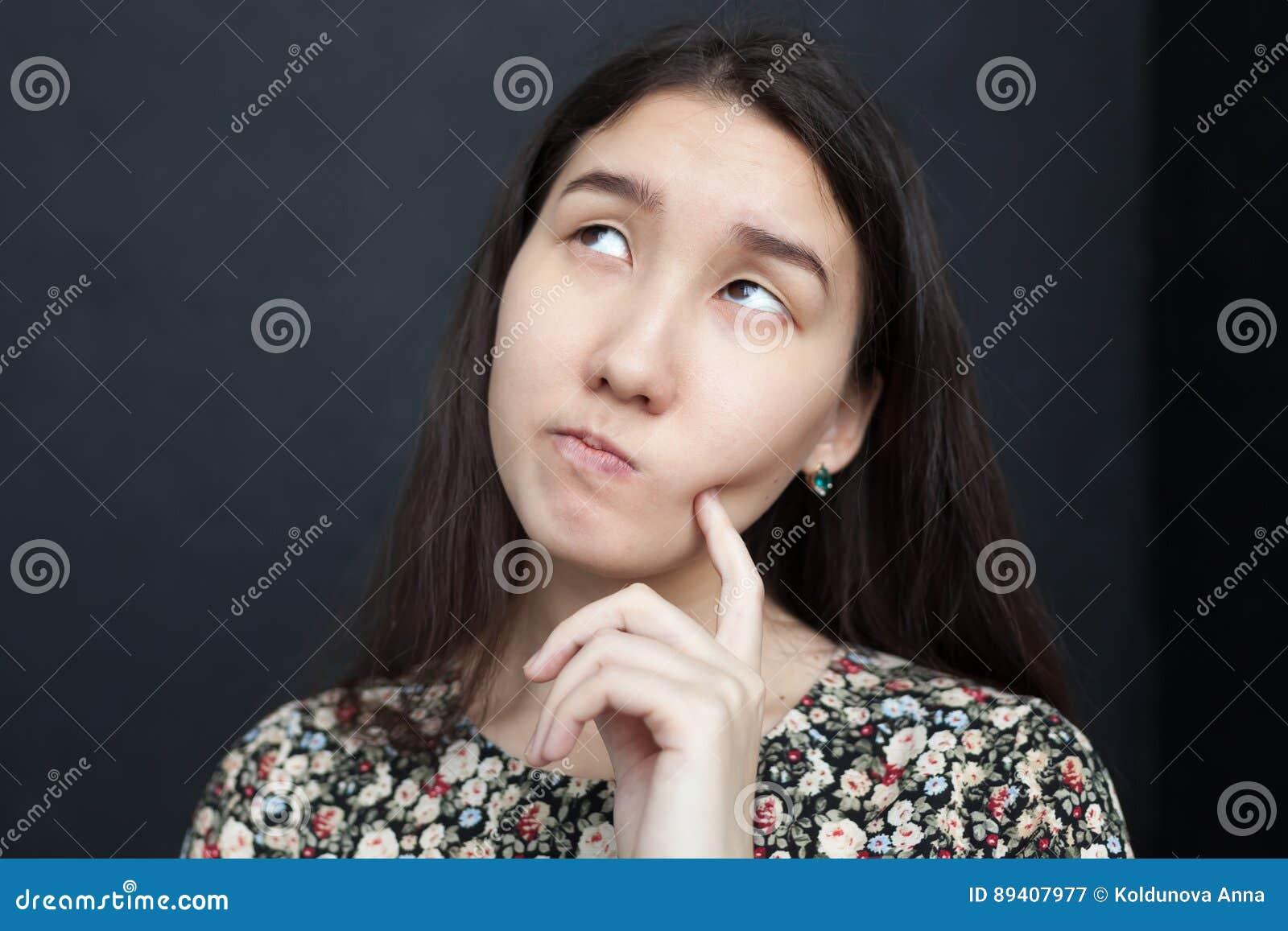 A menina asiática olha acima pensativamente, duvidando a decisão Fricciona seu queixo na incerteza