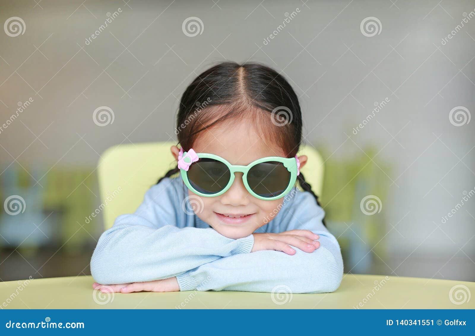 Menina asiática pequena adorável da criança que coloca em vidros de sol vestindo da tabela das crianças com sorriso e vista da câ