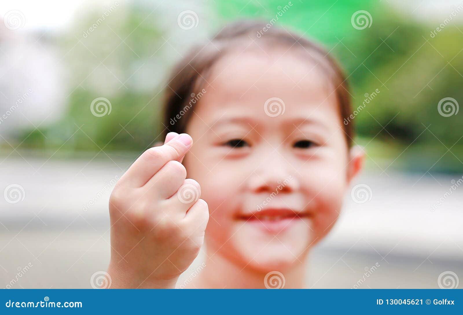 Menina asiática pequena adorável da criança que faz o mini sinal do coração pelo polegar e pelo dedo indicador para eu te amo Foc