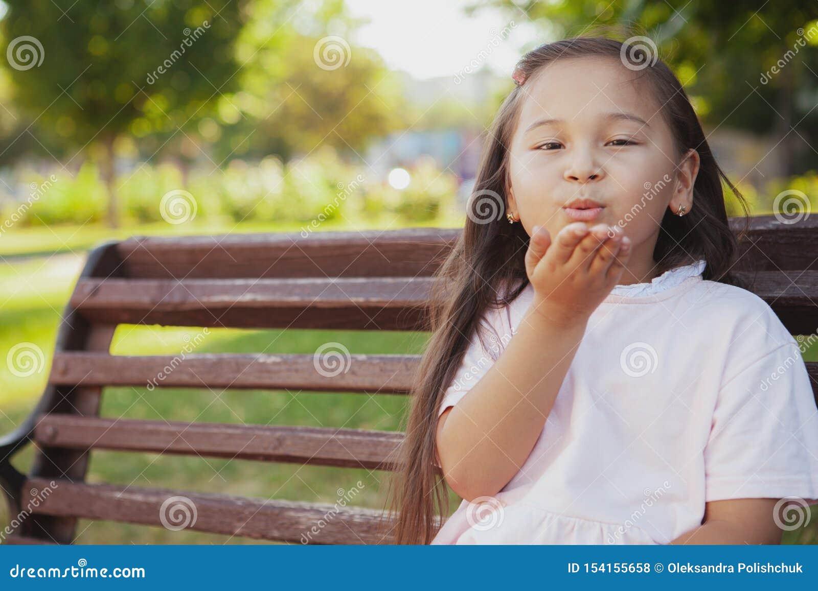 Menina asiática pequena bonita no parque em um dia de verão