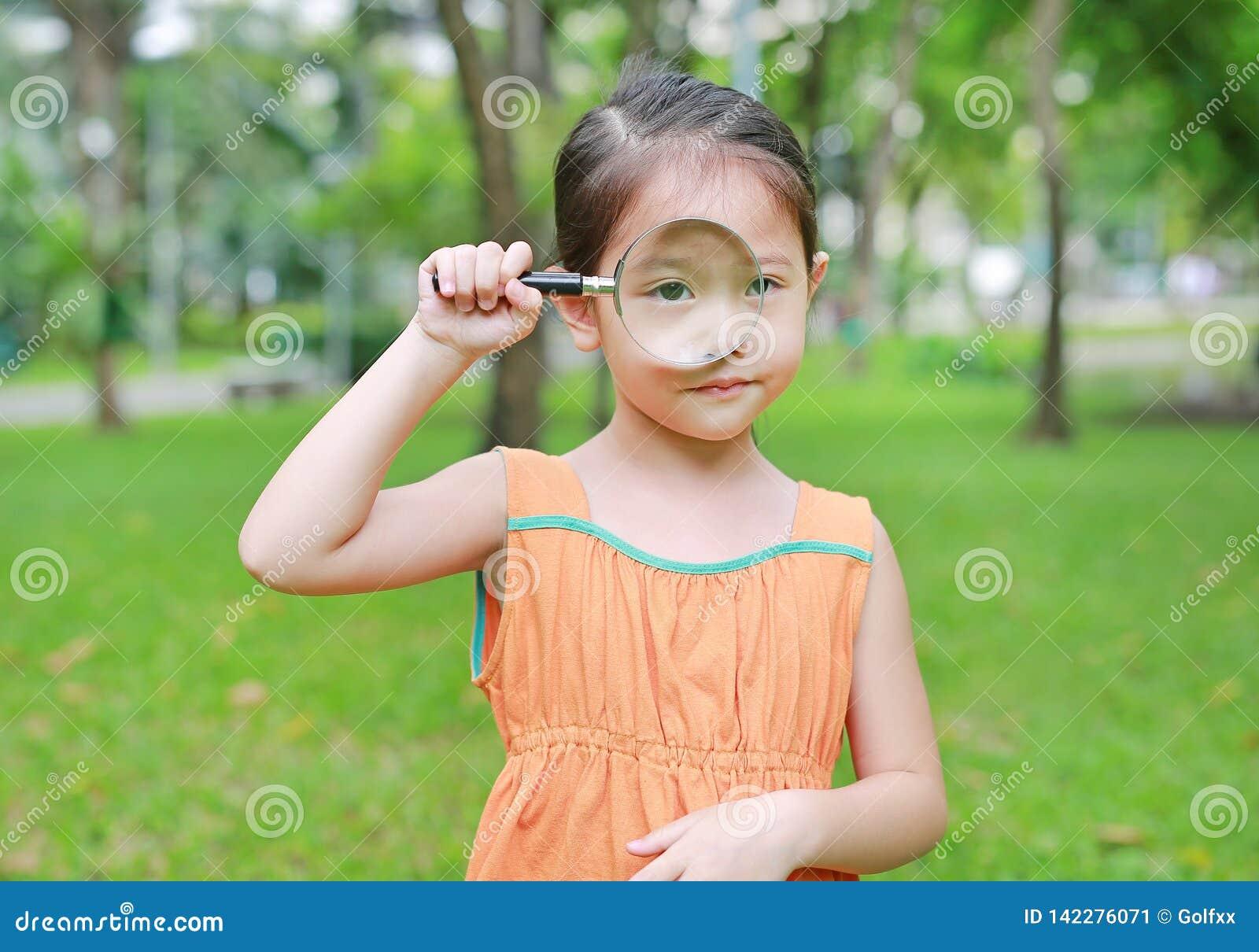 Menina asiática pequena bonito da criança que olha através do vidro magnifiying sobre na grama fora