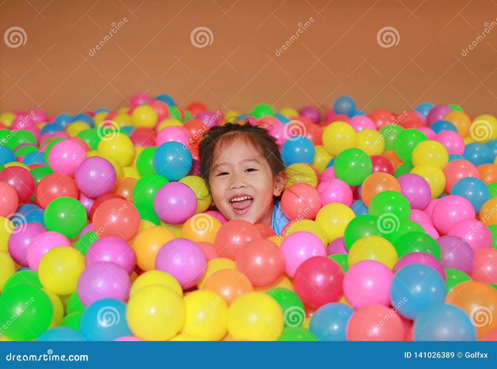 Menina asiática pequena feliz da criança que joga com o campo de jogos plástico colorido das bolas