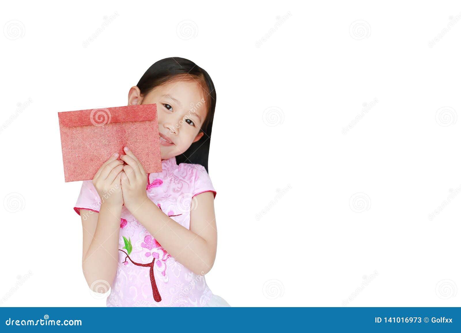 Menina asiática pequena feliz da criança que veste o vestido tradicional cor-de-rosa do cheongsam que sorri ao receber o envelope